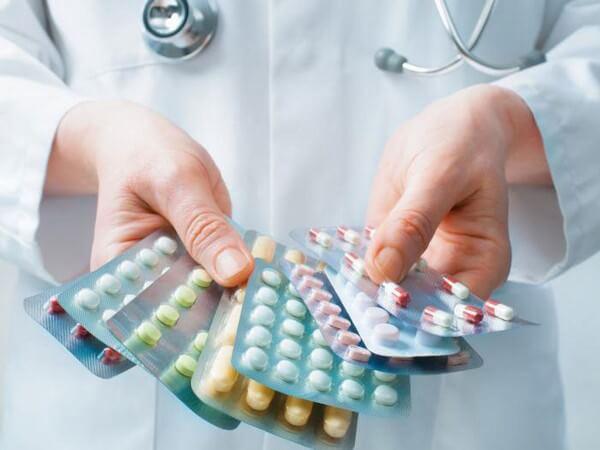 упаковки с таблетками в руках
